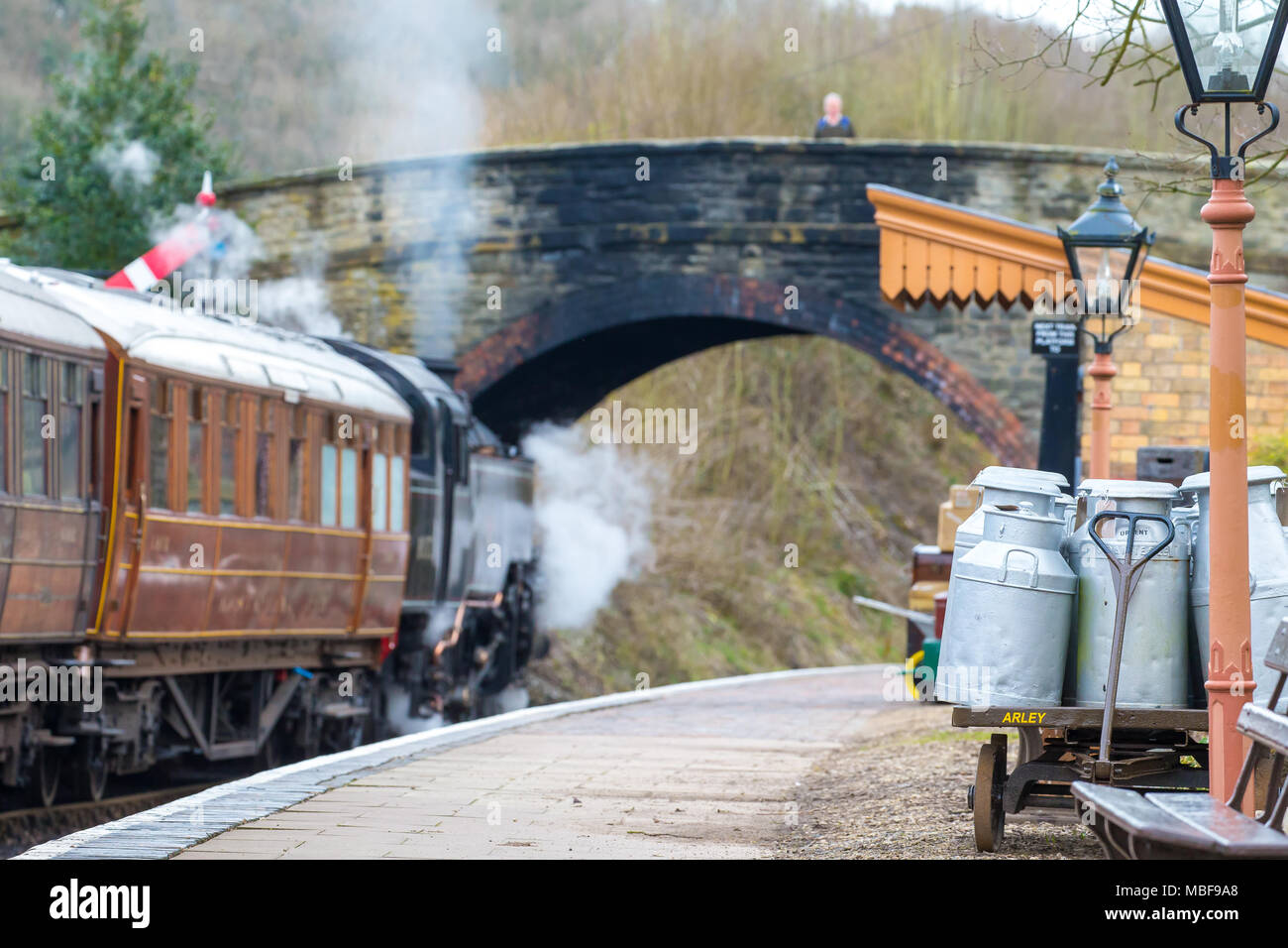 Milk churns (period artefacts) on platform of Severn Valley Railway Arley station. A steam locomotive travels past as a man views from bridge above. - Stock Image