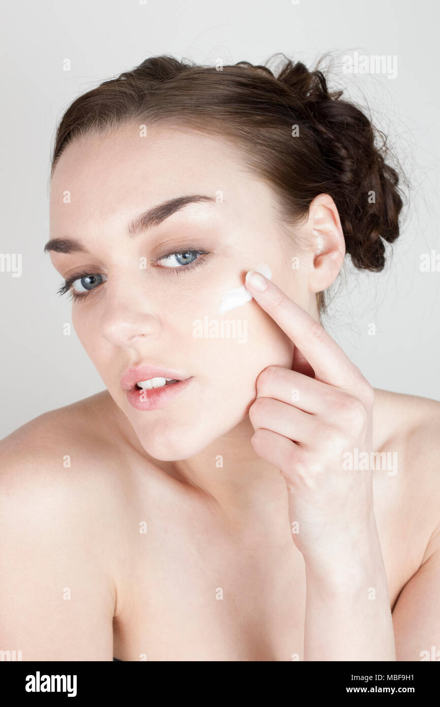 Woman applying face cream and looking towards the camera into a mirror - Stock Image