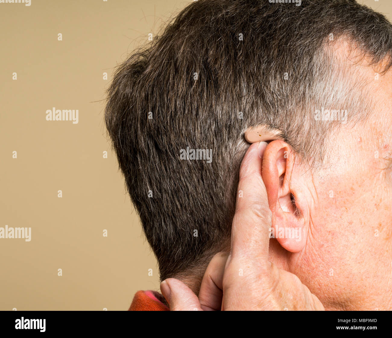 Senior man wearing a small modern hearing aid hidden behind the ear - Stock Image