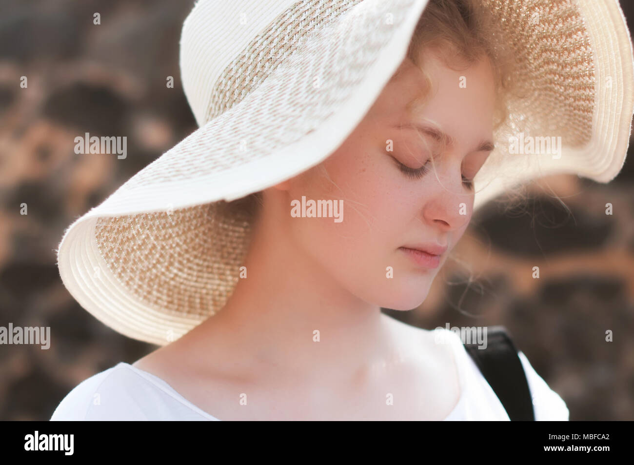 b82f8549748 A natural warm portrait of a beautiful young blonde girl in a summer straw  hat with