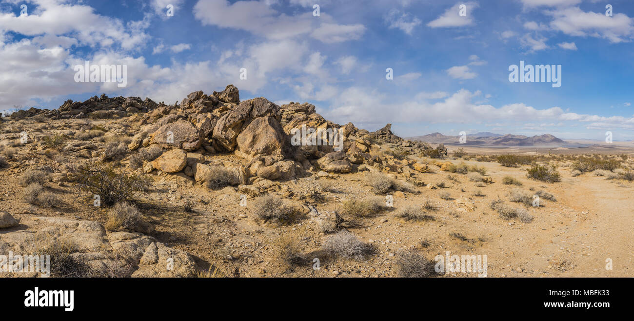 Desert panorama shows dirt trail and boulder rock pile in southern California. - Stock Image