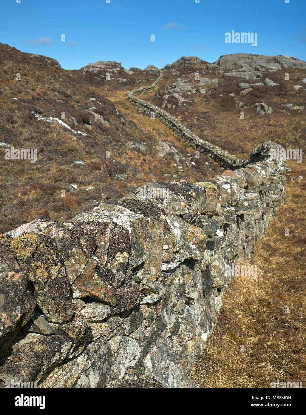 Unusual stone wall constructed of granite boulders winds its way through the rocky landscape of Uig on The Isle of Lewis, Scotland. - Stock Image