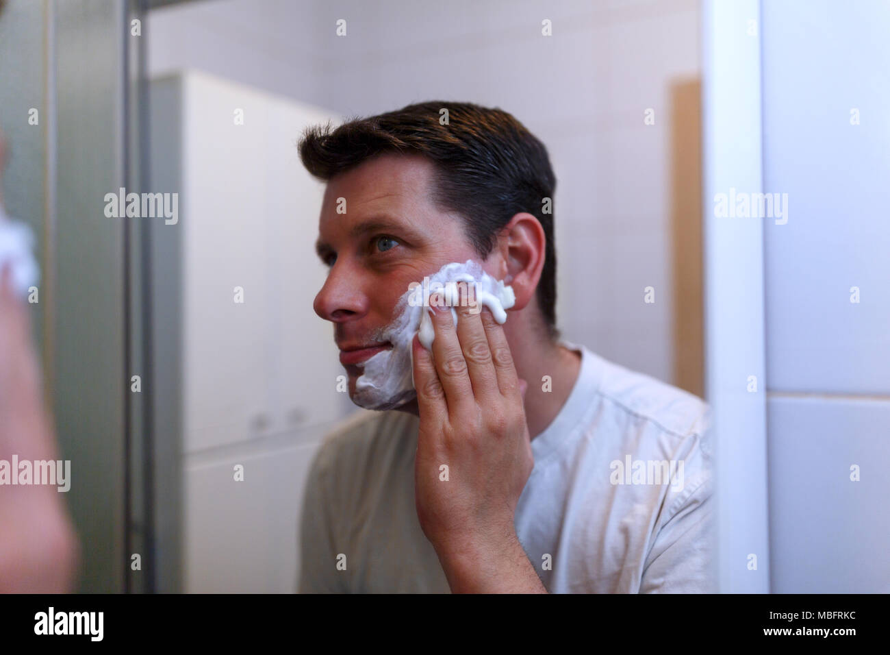 Happy handsome man shaving in bathroom - Stock Image