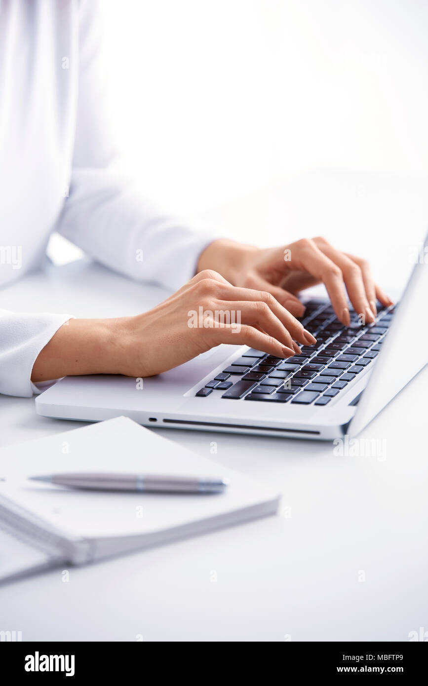 Close-up of businesswoman's hand typing on the keyboard while sitting at office desk. Stock Photo