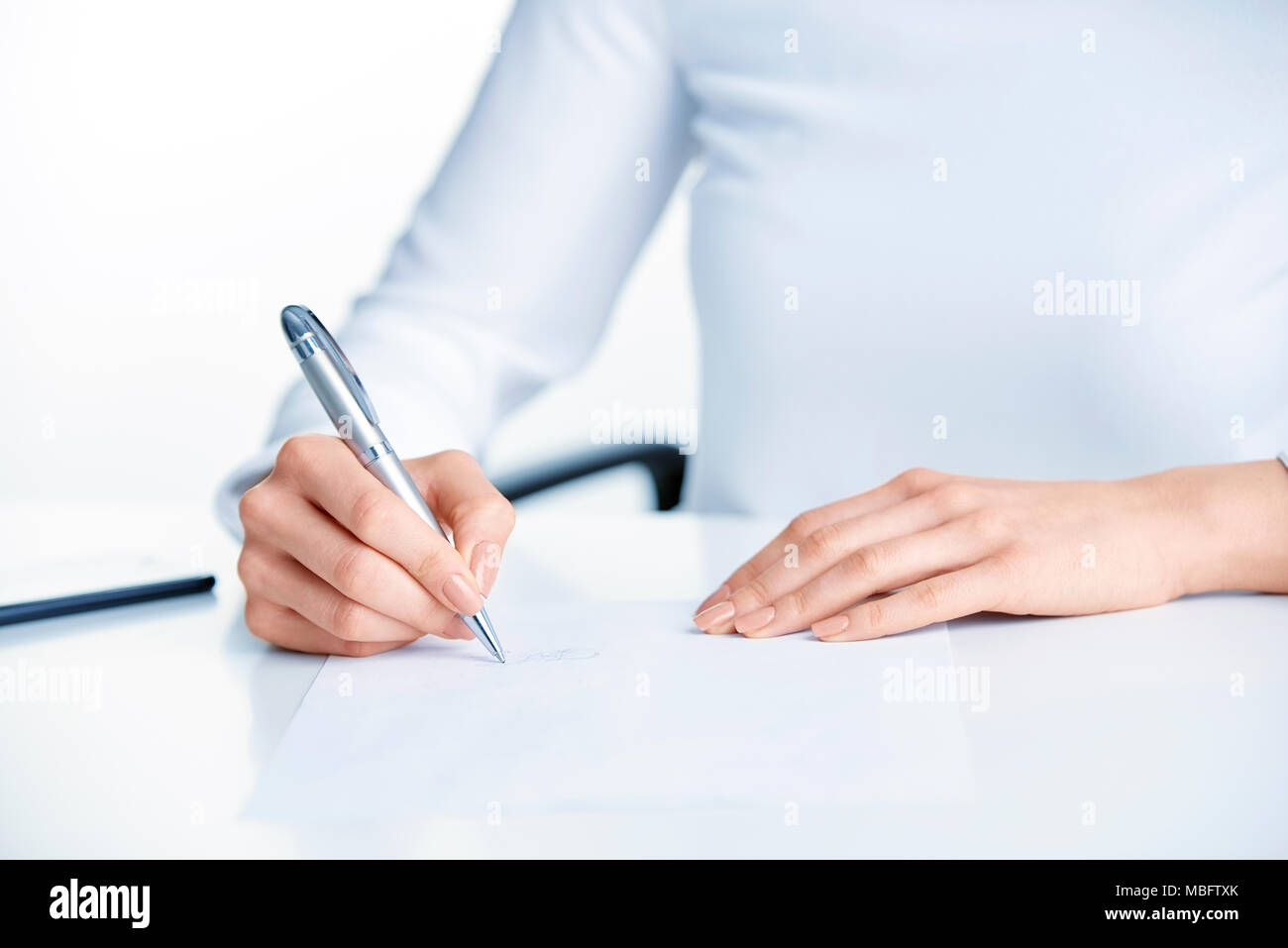 Close-up shot of businesswoman's hand holding pen and sign the paper while sitting at office desk. Stock Photo