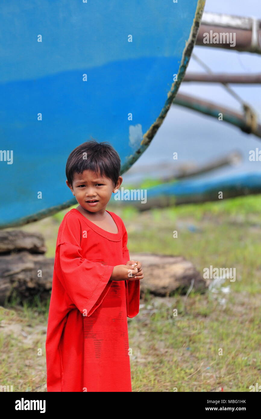Sipalay, Philippines-October 13, 2016: Filipino young boy plays among and gets  used to the fishing boats that will presumably be his own future instru