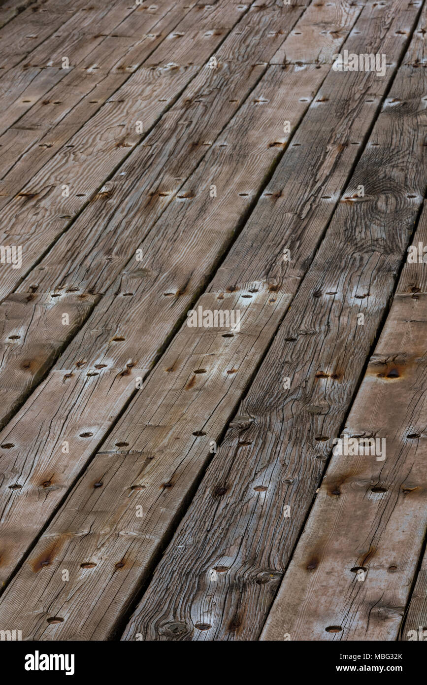 Some old wooden planks forming the deck of an old pier or seaside building jetty. Planked decking with knots and caulking for backgrounds lines. - Stock Image