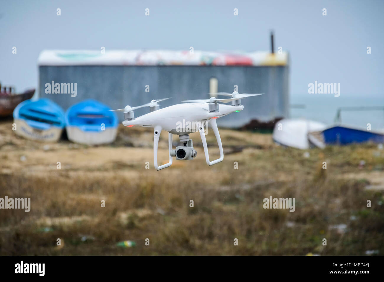 Drone flying in front of a blurry background of boats and depot - Stock Image