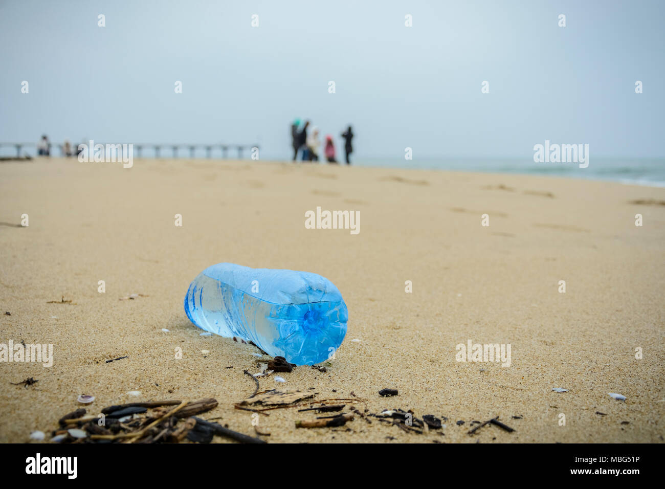 dirty plastic bottle dropped on the beach - Stock Image
