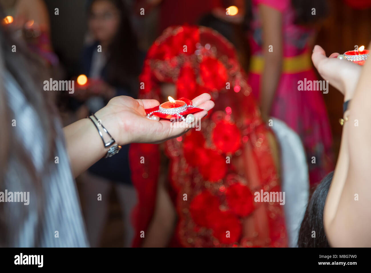 Holding hands on henna candle . She holds the candle in his hand Henna party Stock Photo
