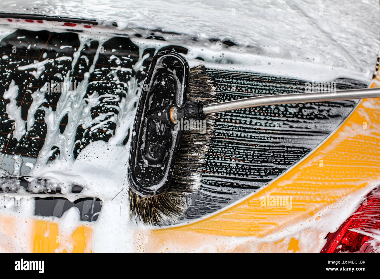 Detail of dark yellow car rear window washed in carwash. Brush leaving strokes in white soap and shampoo foam. - Stock Image