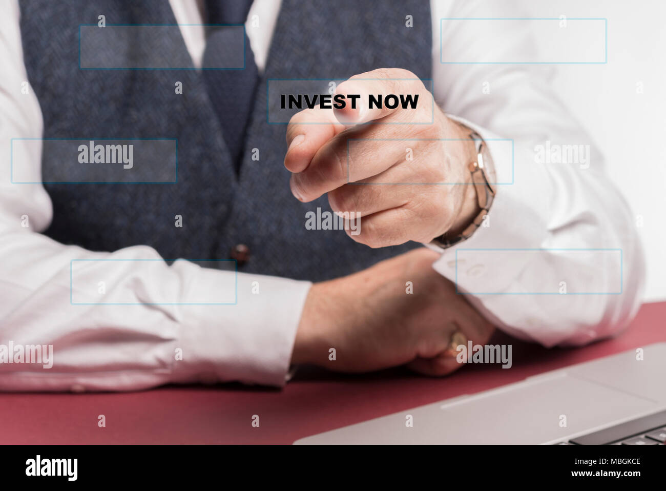 A bussinessman sitting at a desk pressing a virtual button saying invest now. - Stock Image