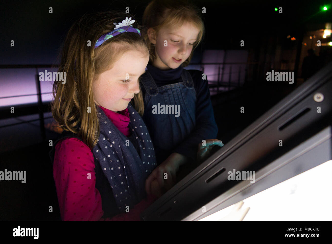 Two young sisters interacting with interactive tourist ship education informational panel inside The Mary Rose Museum. Portsmouth Historic Dockyard UK - Stock Image