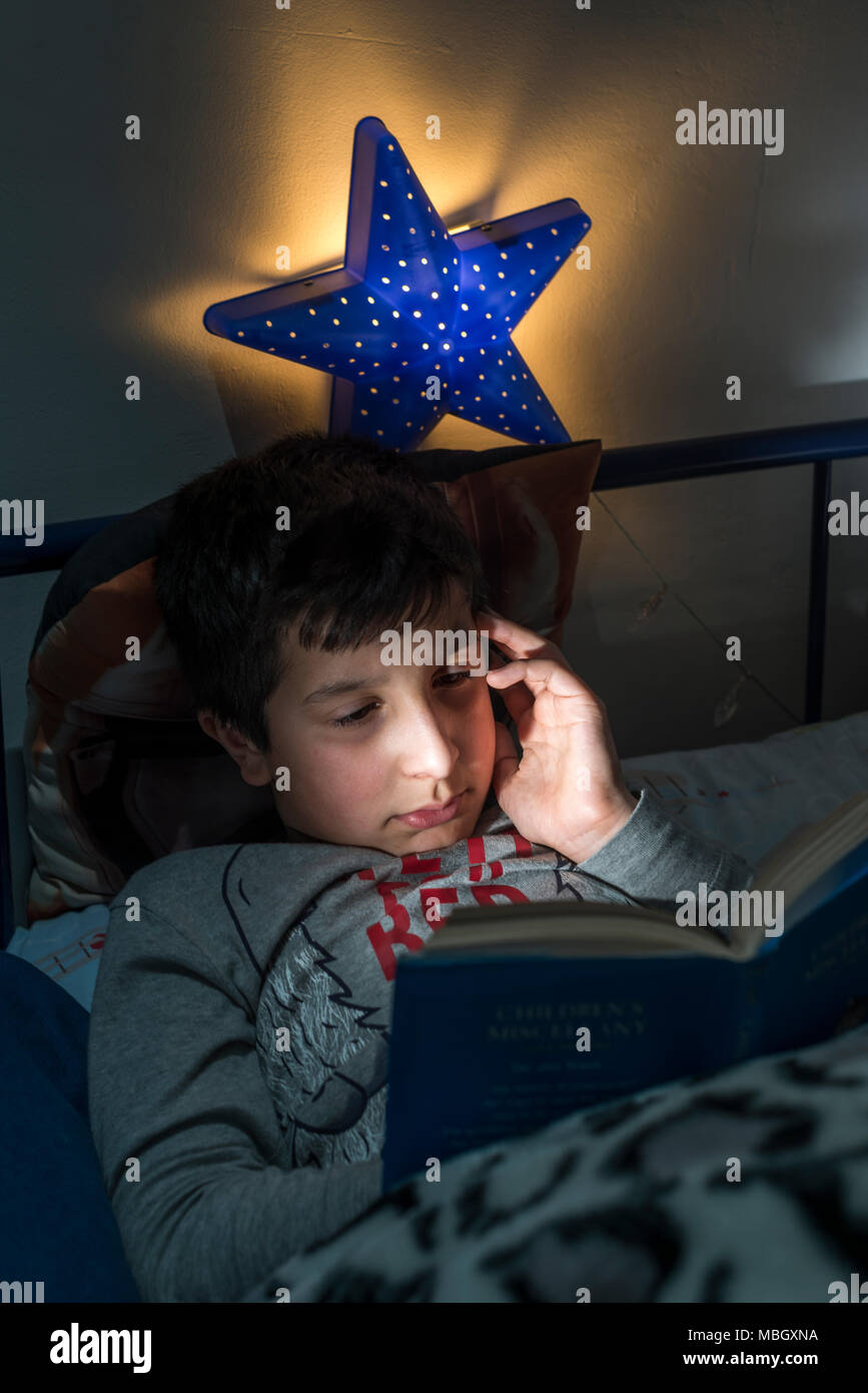 UK,Surrey, boy reads in bed late at night - Stock Image