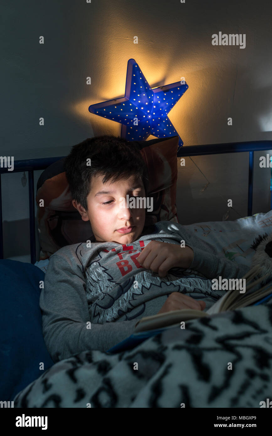 UK,Surrey.10 years boy reads in bed - Stock Image