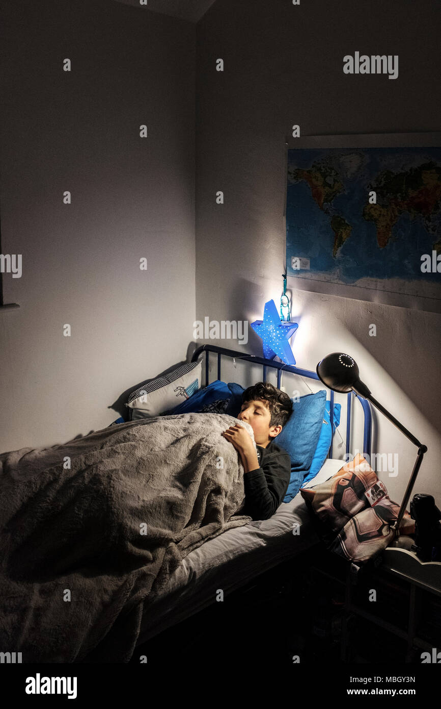 Boy,10 years old sleeps in his room with lights on,UK,Surrey - Stock Image