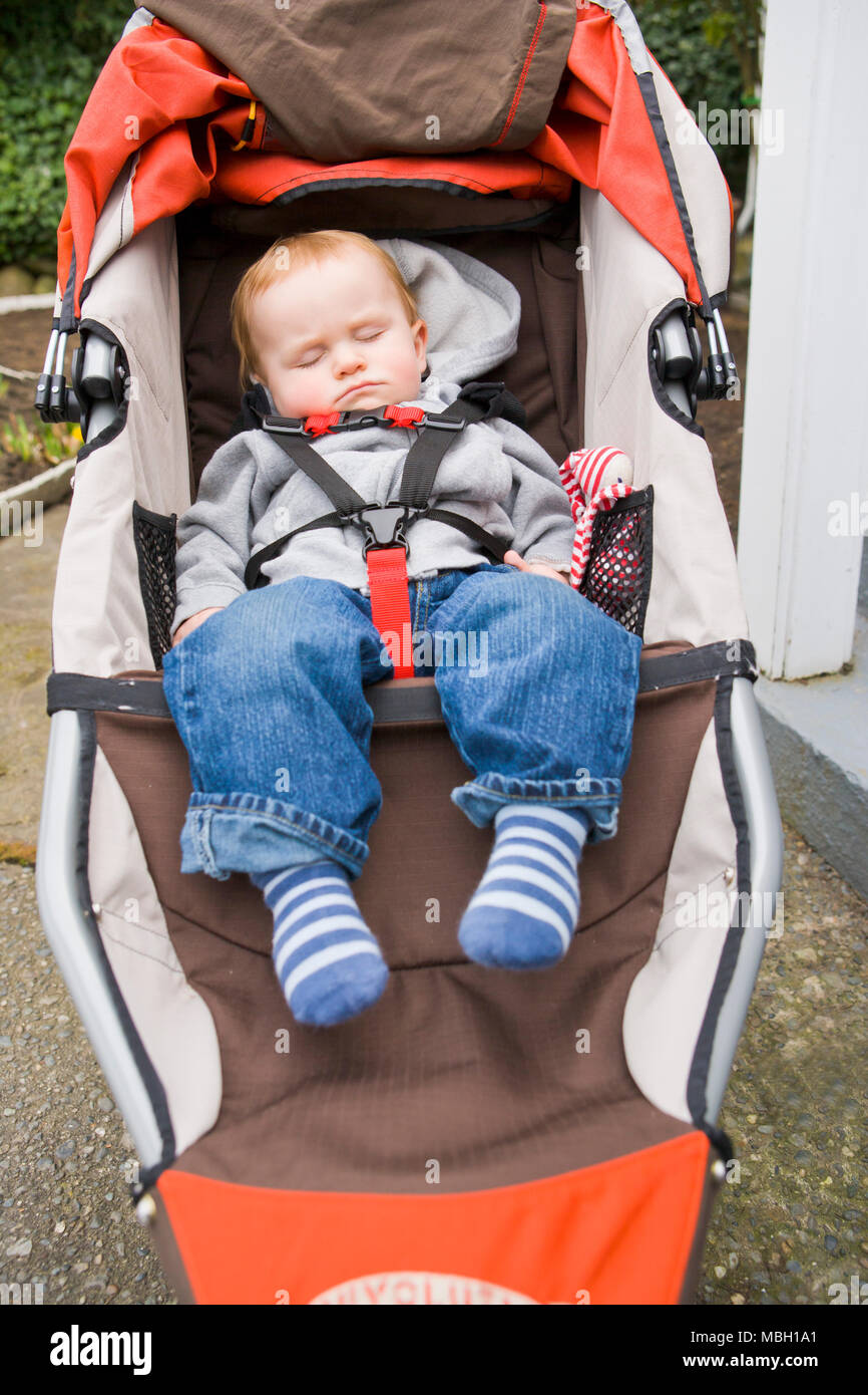 A ten mon th old baby asleep in a running stroller. - Stock Image