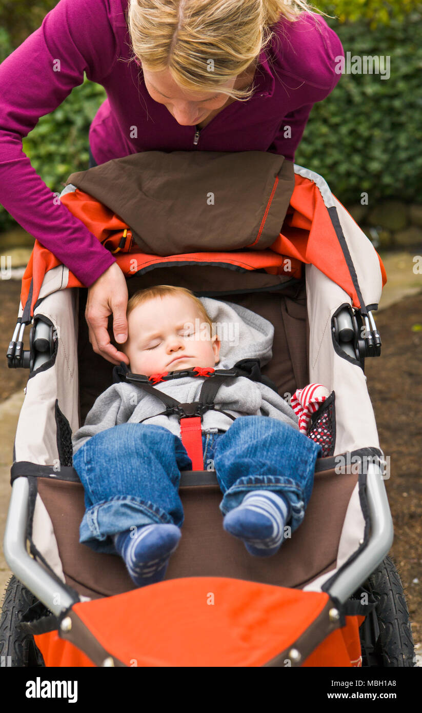 A mother sits on the front stairs talking on her cell phone while a baby boy sleeps in a running stroller. - Stock Image