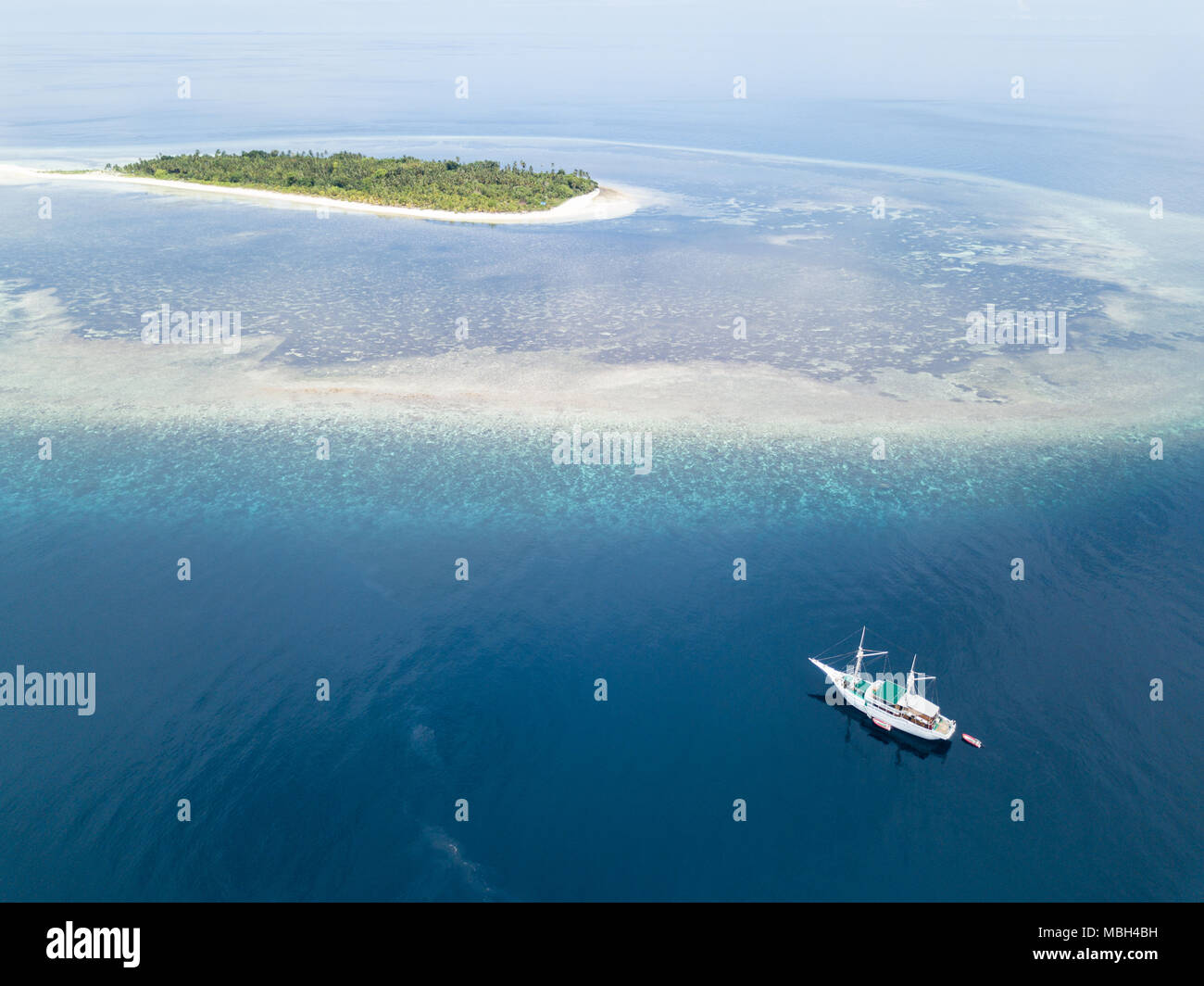 A Pinisi schooner drifts near a remote, tropical island in the Banda Sea. This region is in the Coral Triangle and has high marine biodiversity. - Stock Image