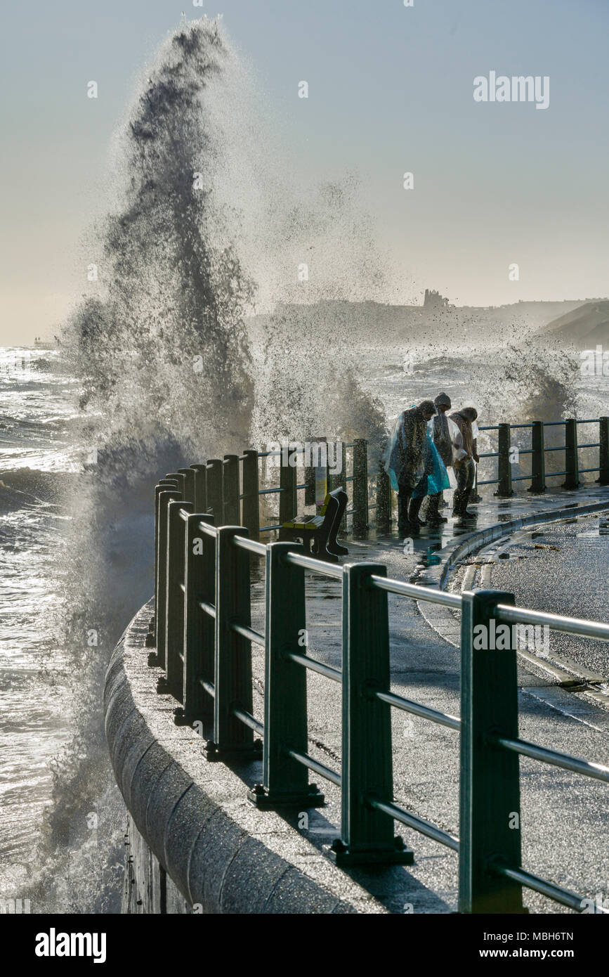High tide and huge waves crashing over the sea wall and people at Sandsend North Yorkshire, UK - Stock Image