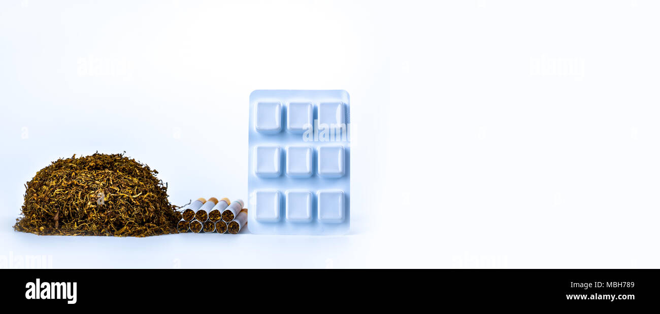 Nicotine chewing gum in blister pack near pile of cigarette. Quit smoking by use nicotine gum for relief of nicotine withdrawal symptoms. Medicine for - Stock Image