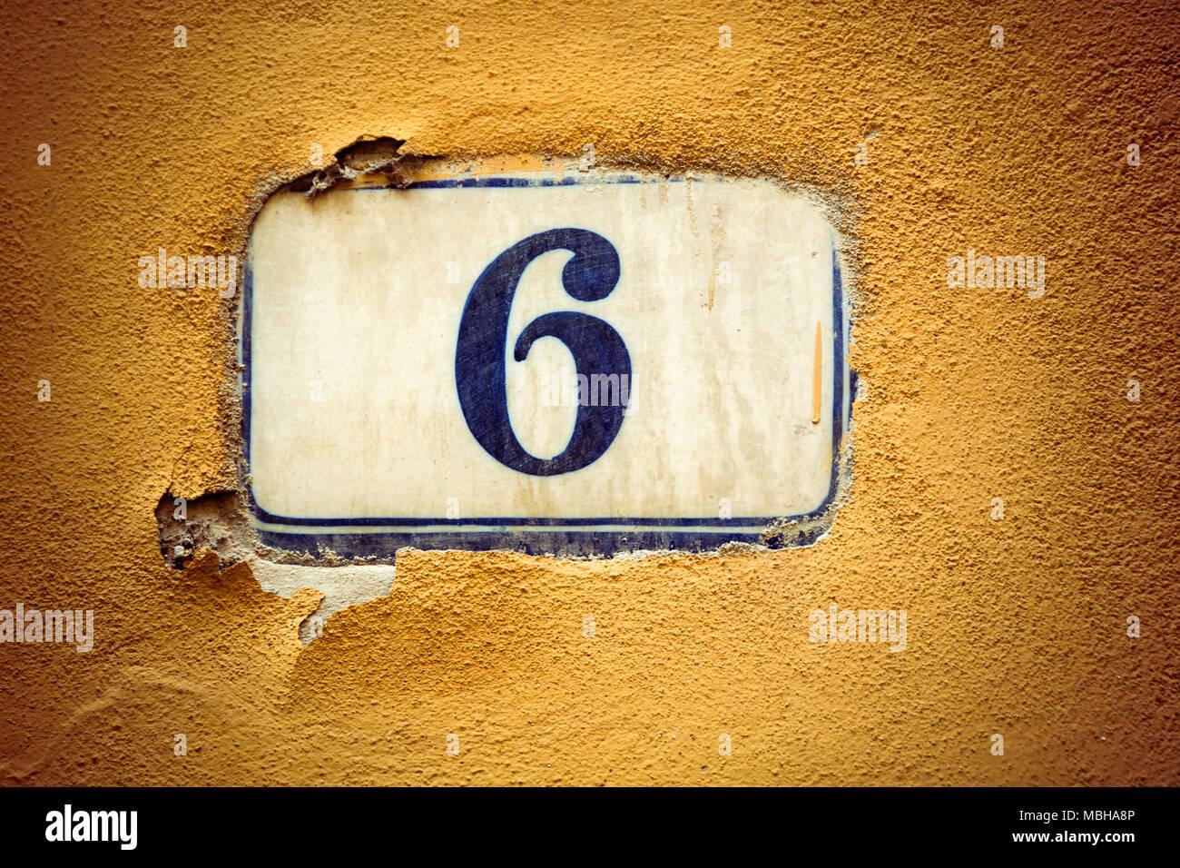 Number six enamel door number on plaster wall - Stock Image