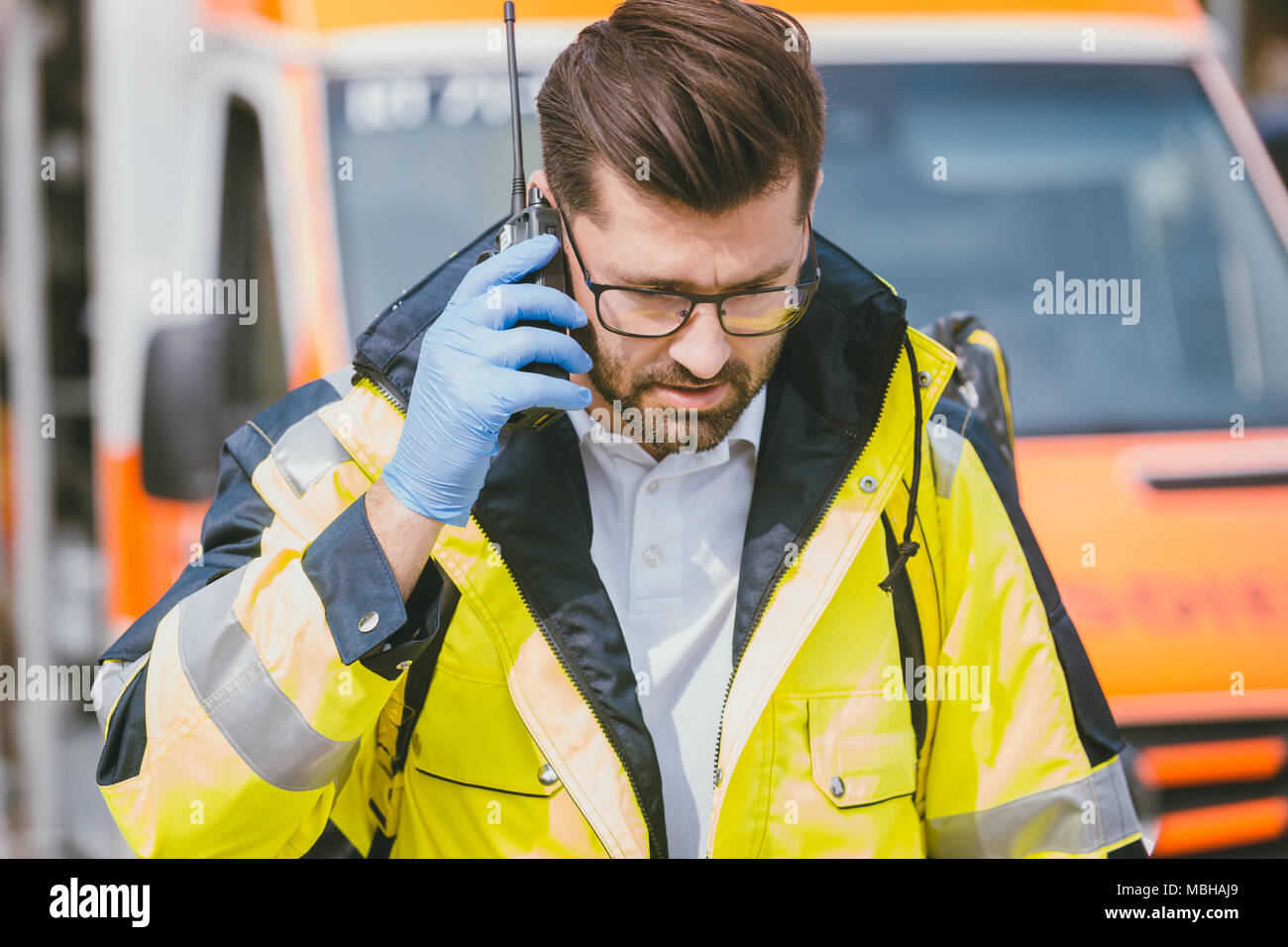 Medic talking to headquarter via radio in front of ambulance - Stock Image