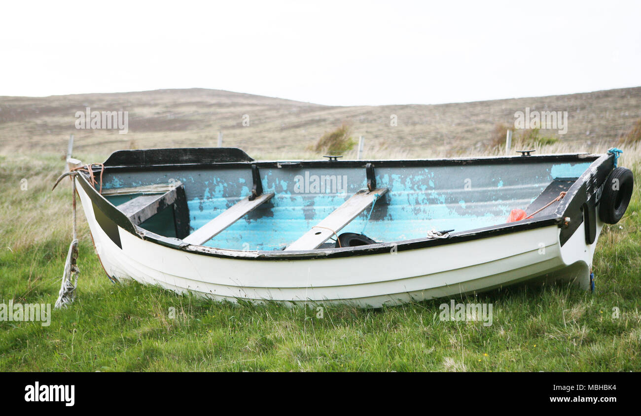 Small dinghy boat on a green field - Stock Image