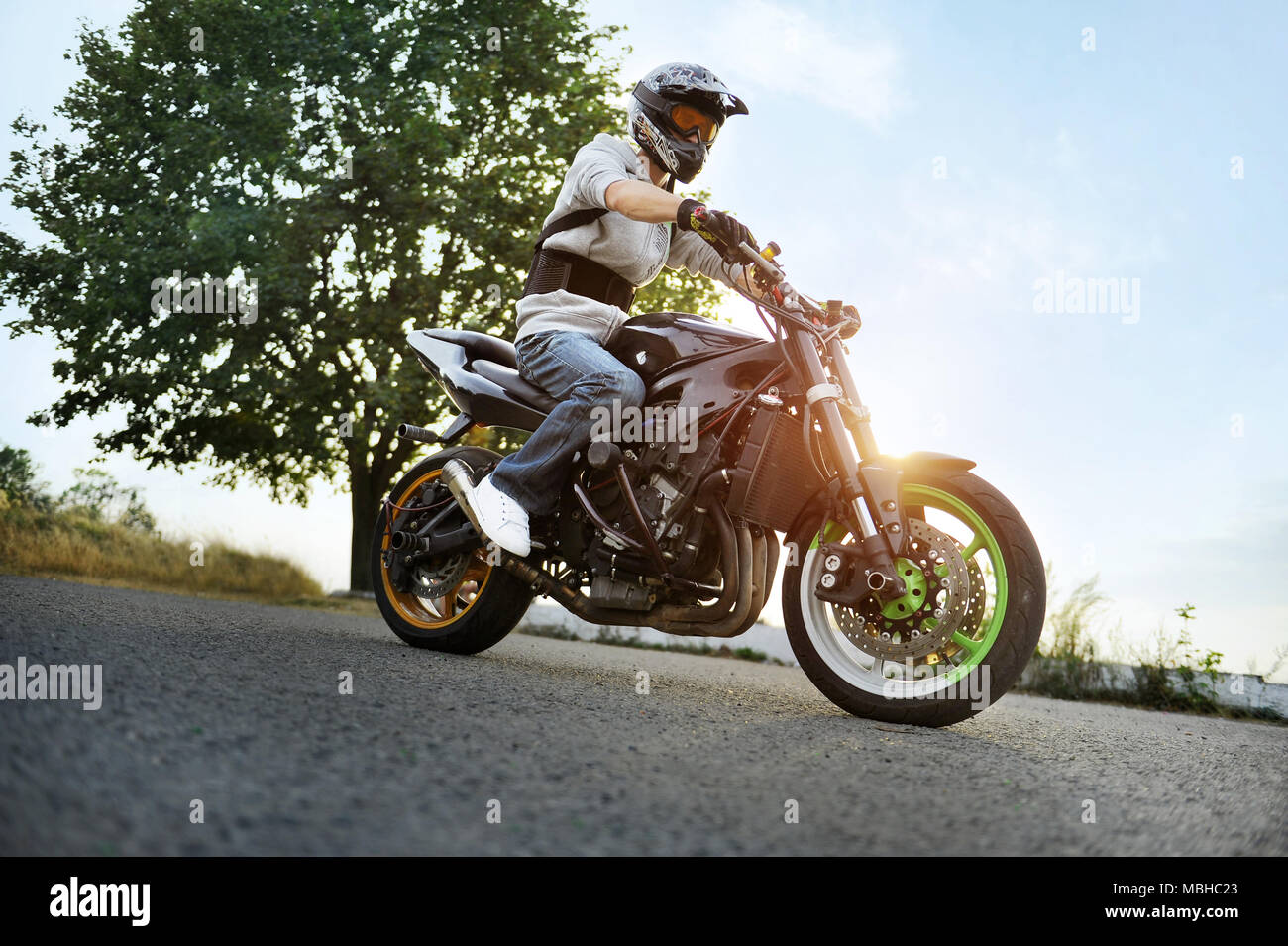 Ivano-Frankivsk, Ukraine - 28 August 2015 : Photo of biker, wearing protective helmet is sitting on his colorful sport motorcycle standing on summer road, filled with shine of sunset. Stock Photo