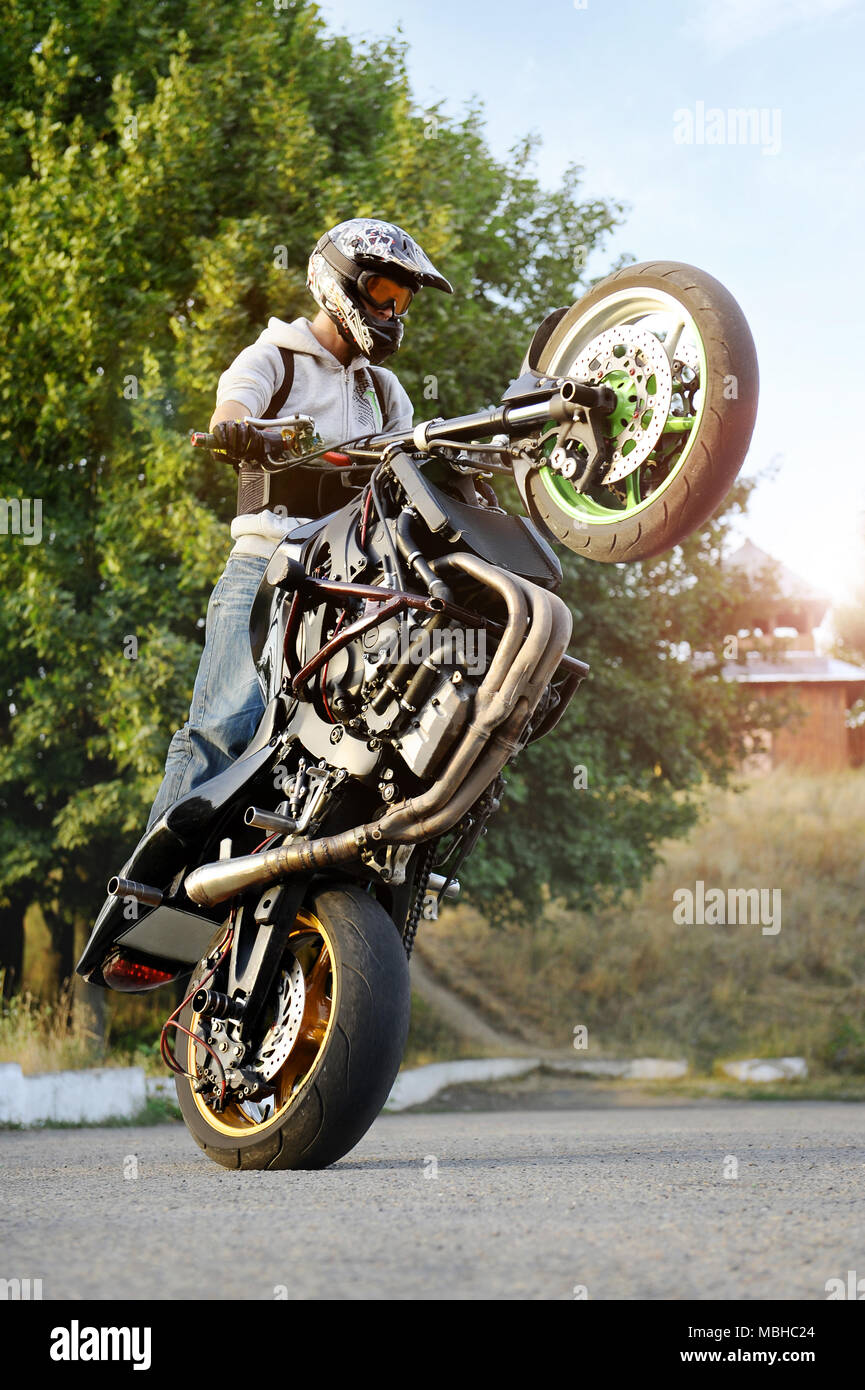 Ivano-Frankivsk, Ukraine - 28 August 2015 : Amazing sideview of practising extreme motorcycle trick biker. Man showing off his talents riding on the street during summer sunny evening. - Stock Image