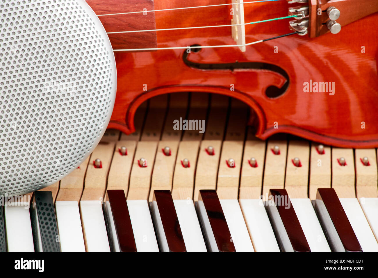 Modern Speaker And Classical Violin On White Black Piano Keys Close Up Background