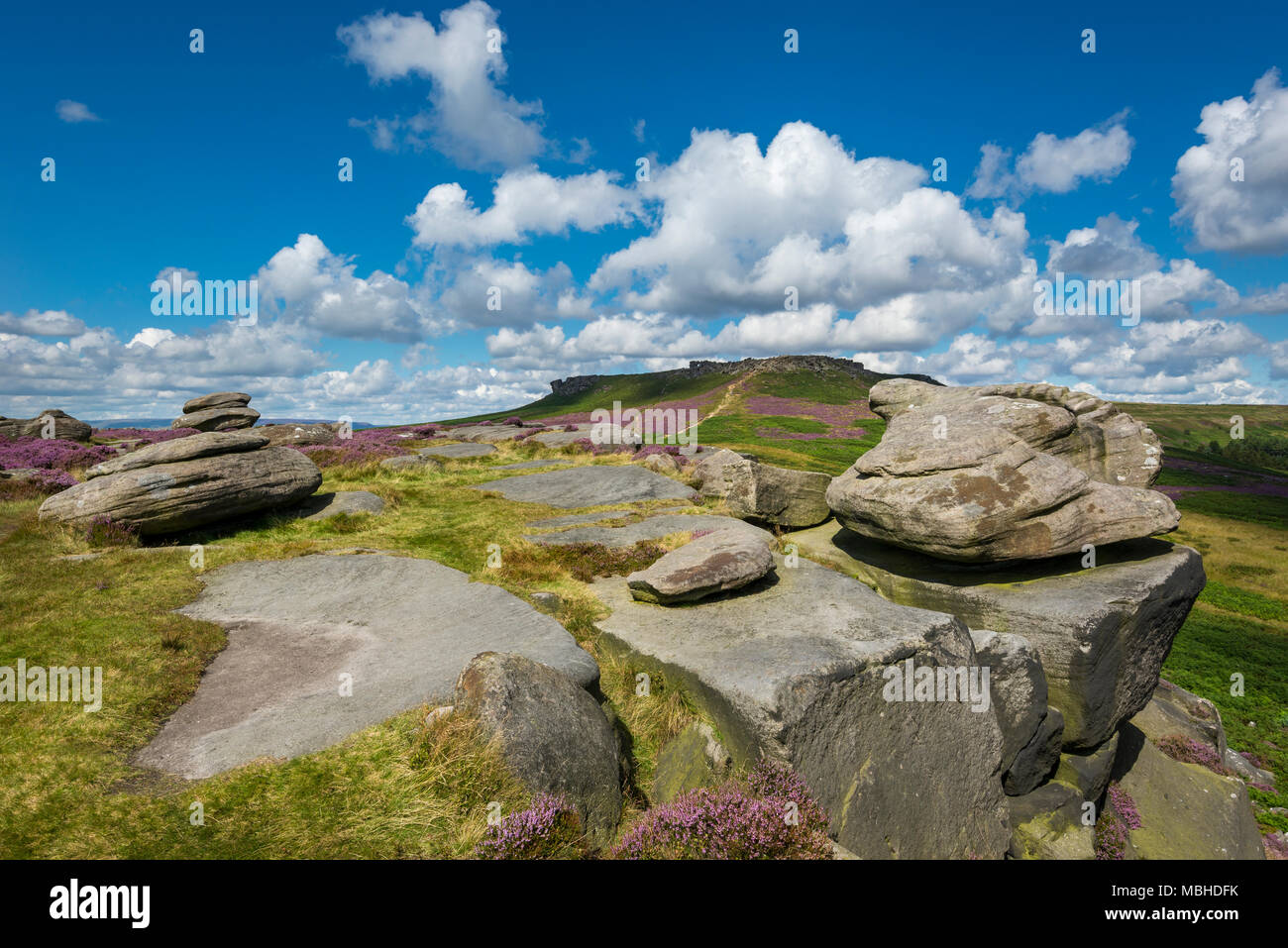 Higger Tor viewed from Carl Wark near Hathersage in the Peak District national park, Derbyshire, England. Summer day with heather in full bloom. - Stock Image