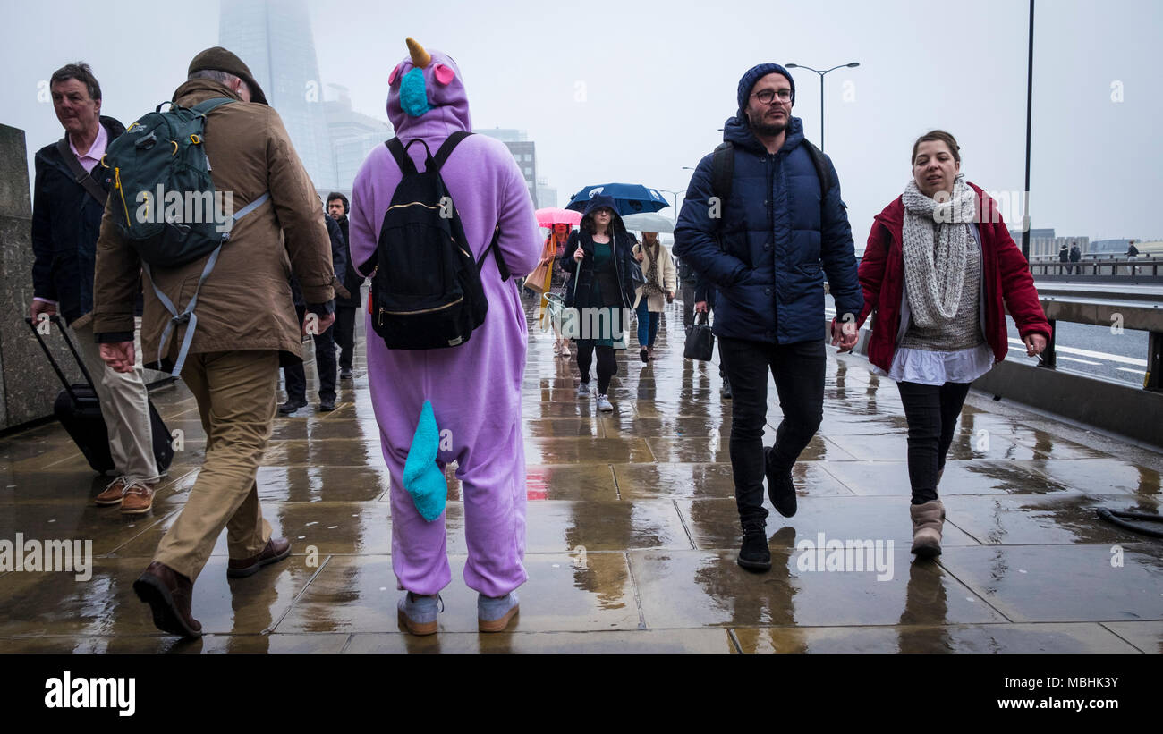 London, UK. 11th April 2018. UK Weather: A fundraiser for the Meningitis Research Foundation stands on London Bridge as passing commuters make their way to work on a drizzly day in the capital (c) Paul Swinney/Alamy Live News - Stock Image