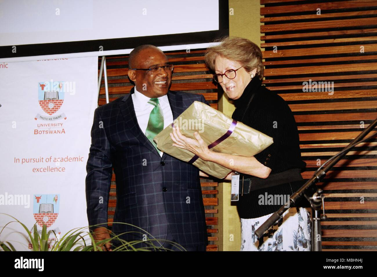 Gaborone, Botswana. 9th Apr, 2018. Professor Thelma Krug, Vice Chair of the Inter-governmental Panel on Climate Change (IPCC) receiving a gift from Professor David Norris, Vice Chancellor of the University of Botswana today after delivering a speech IPCC Assessments, during the official opening of the 4th Lead Author Meeting (LAM4) for the Special Report on: Global Warming of 1.5 degrees Celsius. The theme for this year is ''˜The Paris Agreement Ambition to limit global warming to well below 20C and the IPCC meeting in Botswana. The event was held at the University of Botswana's Internatio - Stock Image