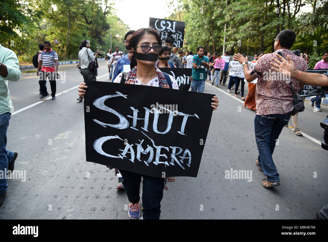 Kolkata, West Bengal, India. 11th Apr, 2018. A woman seen holding a placard during the protest.Hundreds of journalists protest against ruling party's alleged attack on journalists across Bengal during Panchayat nomination coverage. The rally started at Mayo Road Mahatma Gandhi Statue .and culminated at Dorina Crossing in Kolkata. Wearing black bands on arms and covering their mouths with black scarfs, hundreds of city's journalists, cameramen and photojournalists took part in the protest rally. Credit: ZUMA Press, Inc./Alamy Live News Stock Photo