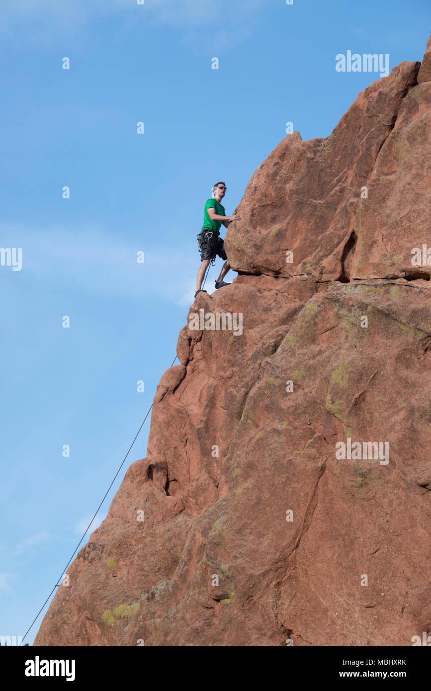Rock Climber man climbing sandstone cliffs in Garden of The Gods April 4, 2016 Stock Photo
