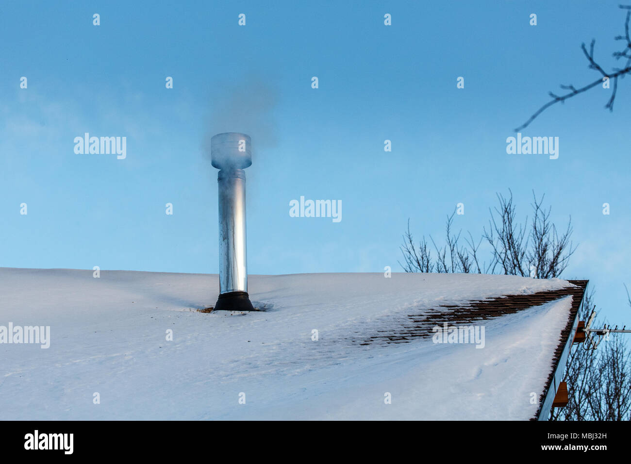chimney on roof with smog and full moon - Stock Image
