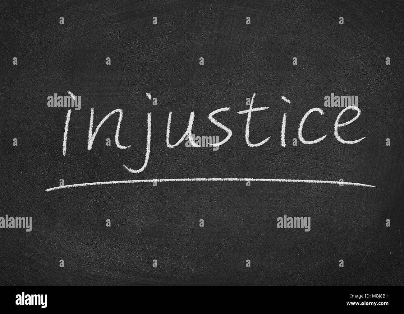 injustice concept word on a blackboard background - Stock Image