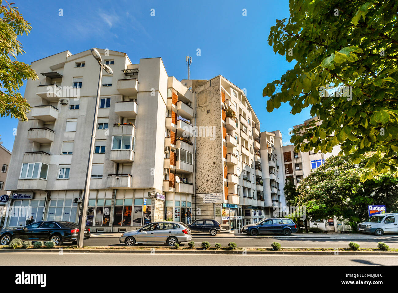A newer apartment building with retail stores still shows the bomb blasts and bullet holes from the Bosnian war in Mostar Bosnia. - Stock Image