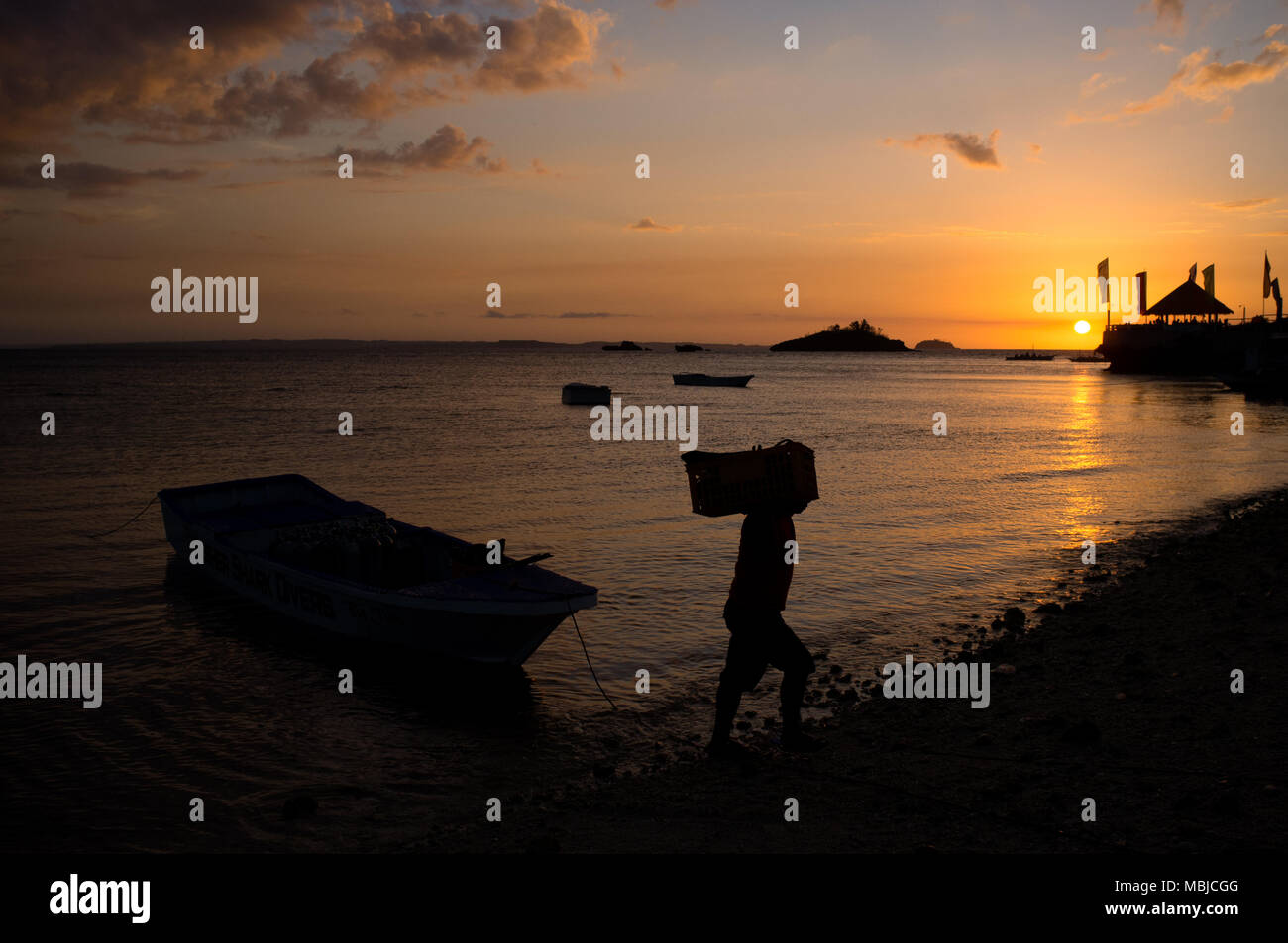 A man carries supplies of food and drink ashore from a boat at