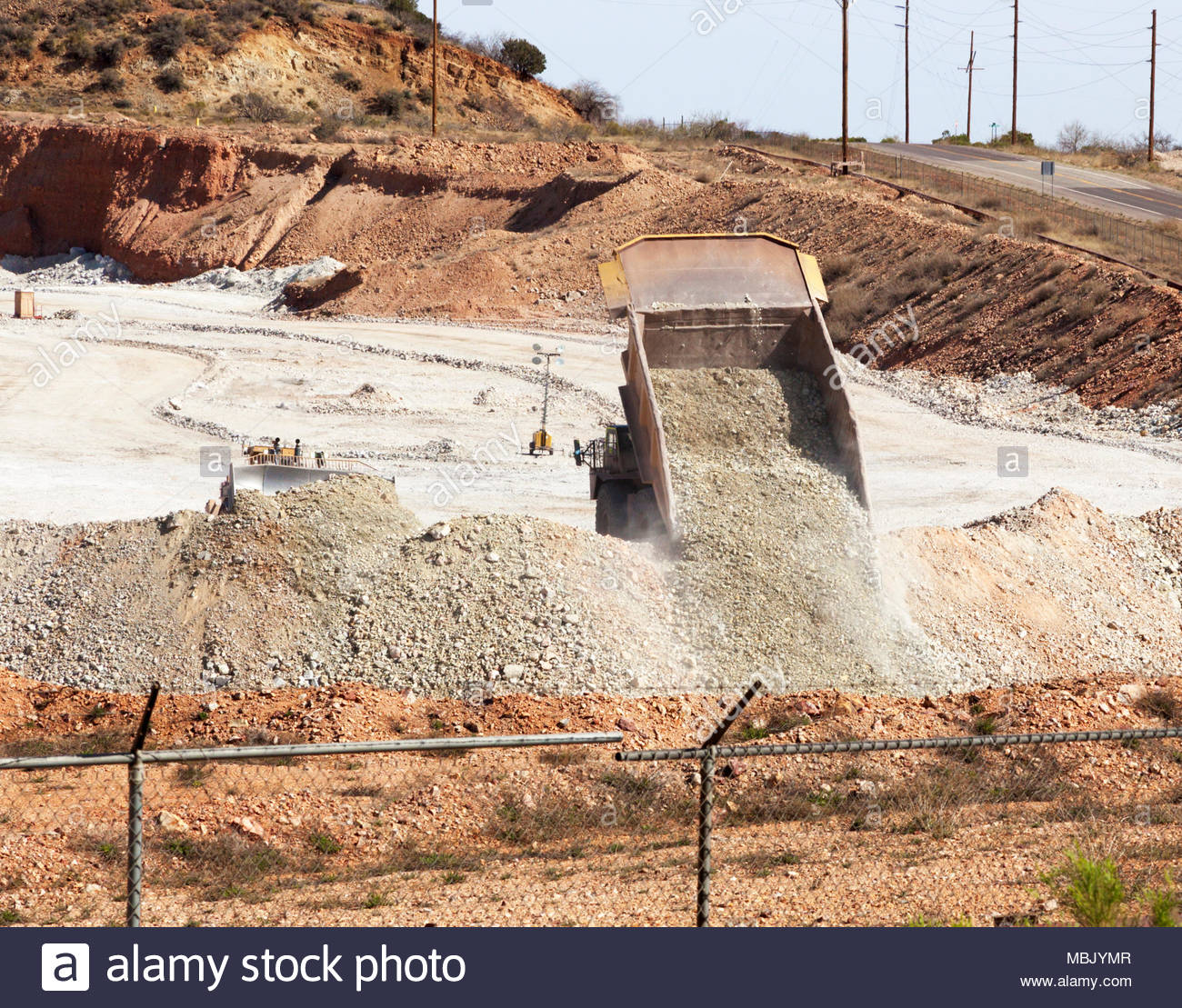 Caterpillar 777D mine haul truck, 100 tons payload capacity, dumping with Caterpillar D11R dozer pushing at left at mine in Arizona, USA - Stock Image