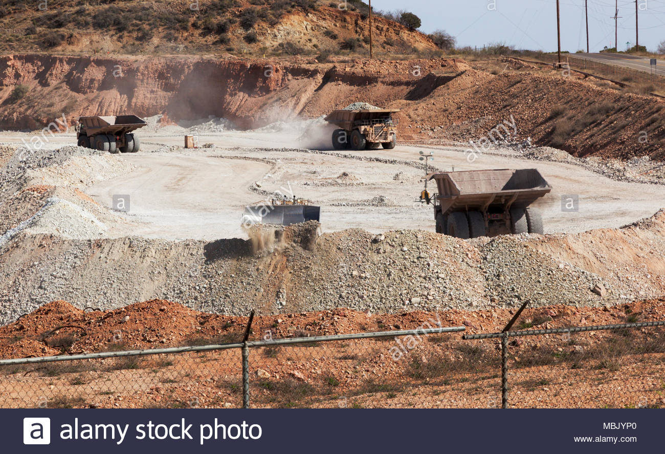 Caterpillar 777D mine haul trucks, 100 tons payload capacity, finished dumping with Caterpillar D11R dozer pushing at left at mine in Arizona, USA - Stock Image
