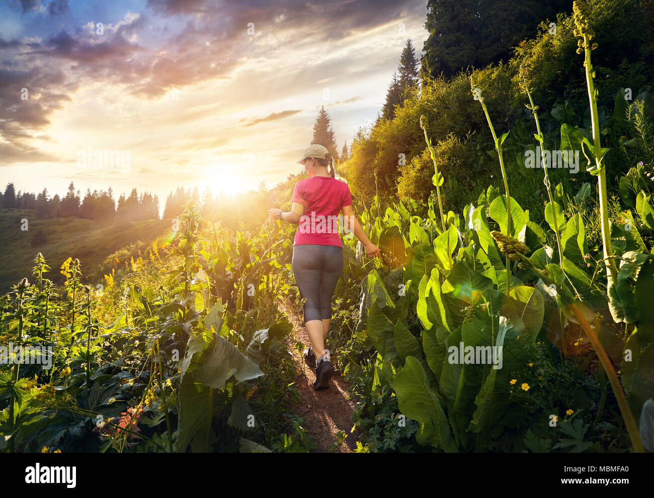Beautiful sporty girl in pink shirt walking in the mountain trail at cloudy sunset sky - Stock Image