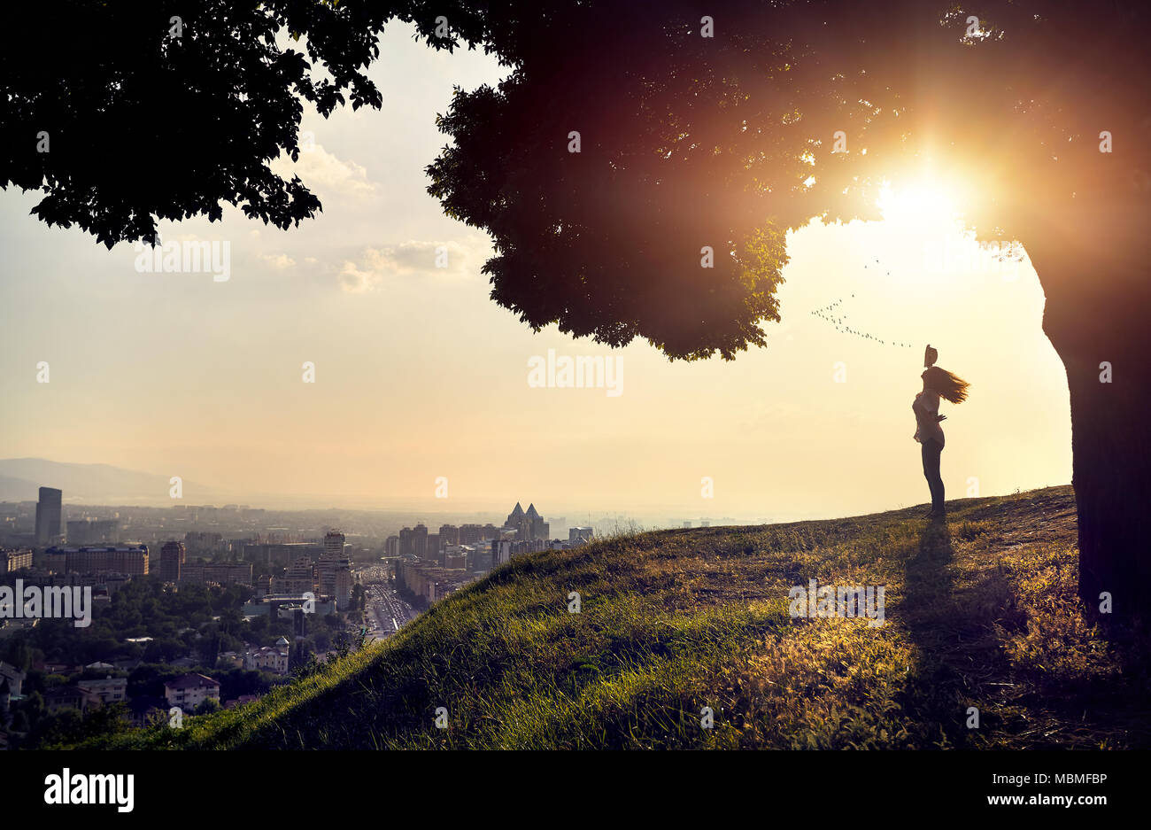 Woman in silhouette with hat rising hand at the sunset city view background. City life concept. - Stock Image