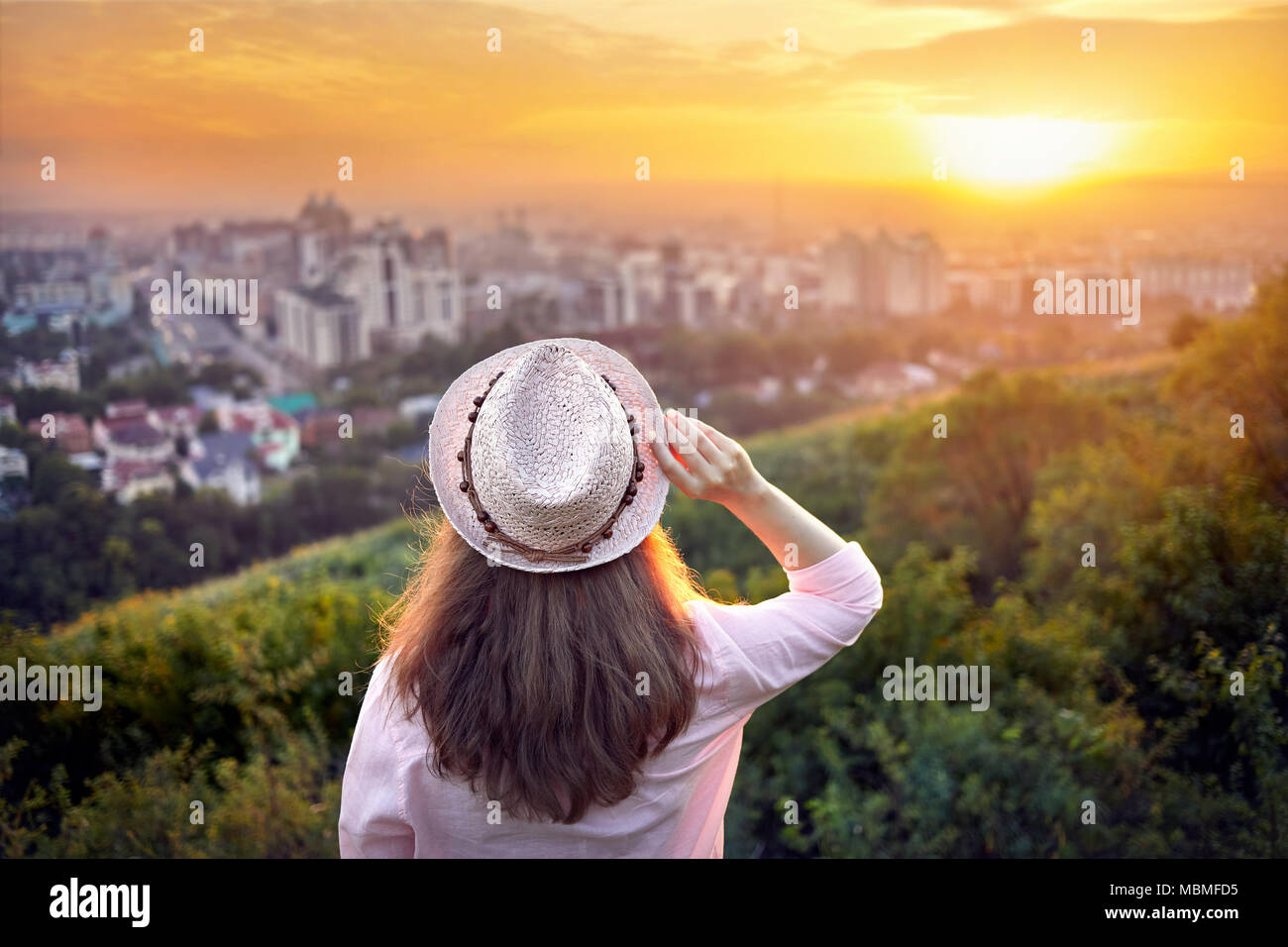 Woman in hat looking at sunset city view background - Stock Image