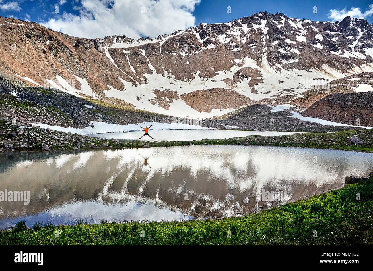 Hiker in orange shirt jumping with rise hand near lake in the snowy mountains - Stock Image