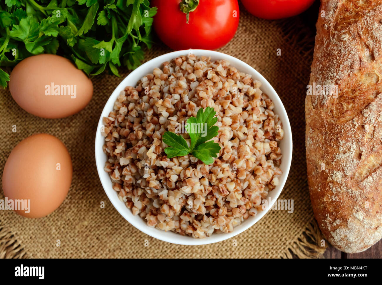 Buckwheat porridge in white bowl. Dietary dish. Vegan. top view - Stock Image