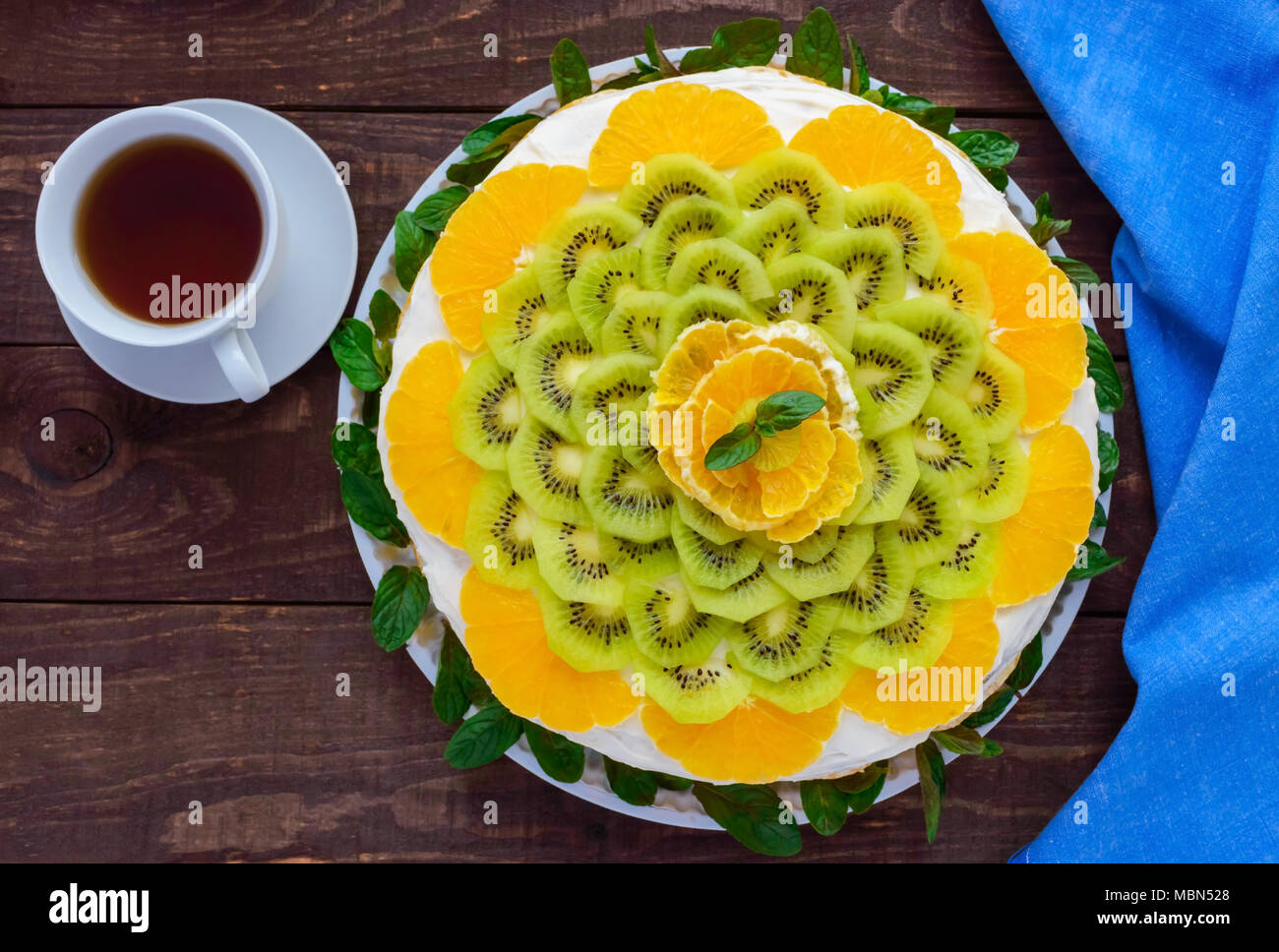 Bright round festive fruit cake decorated with kiwi, orange, mint and a cup of tea. - Stock Image
