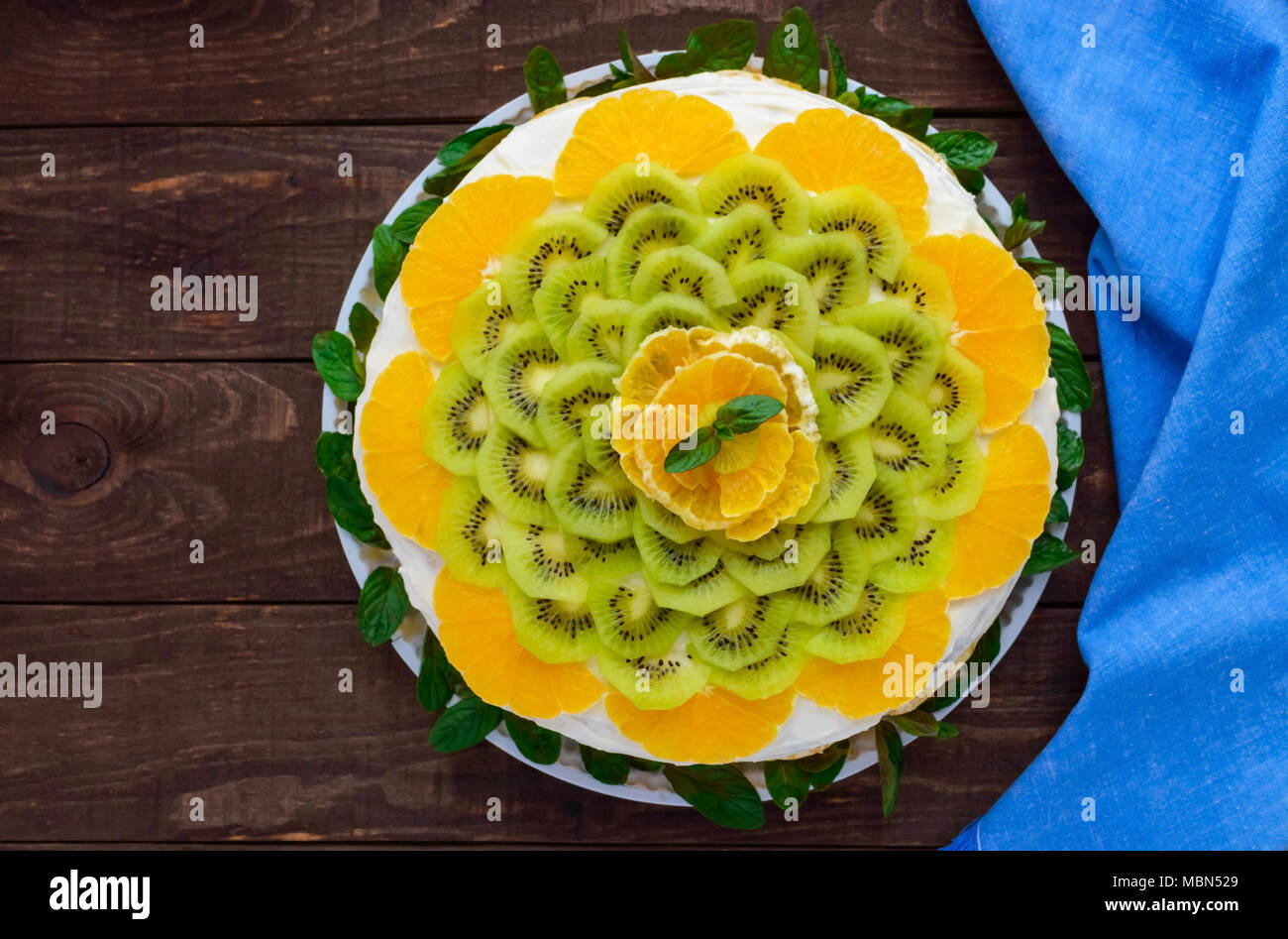 Bright round festive fruit cake decorated with kiwi, orange, mint. The top view. - Stock Image