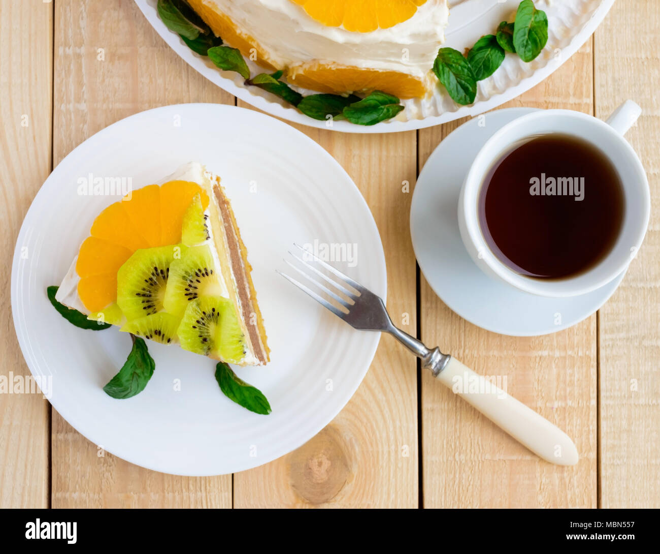 A piece of fruit cake (kiwi, orange, mint leaves) on a white plate on wooden background and a cup of tea. The top view - Stock Image